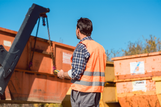Concrete Crushing and Recycling bins with worker operating a machine