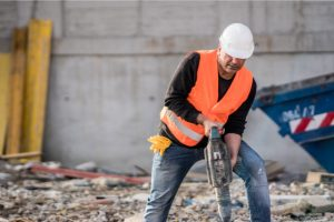 Concrete Demolition worker breaking up concrete with a tool and a hard hat on