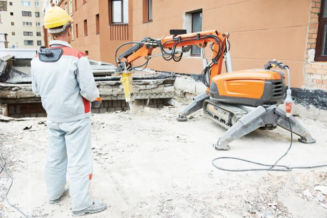 Worker breaking through concrete with a powerful jackhammer machine